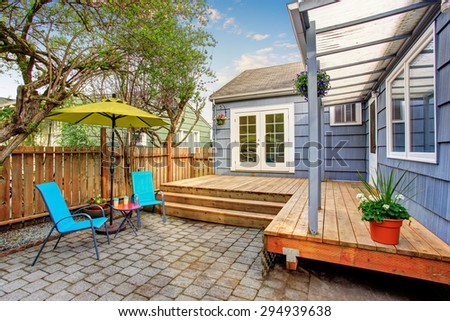 Perfect back deck with concrete patio, umbrella, and chairs.