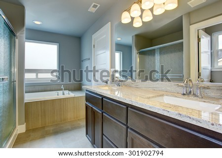 Perfect bathroom with glossy counters, and glass shower. - stock photo