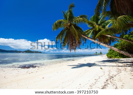 Perfect beach on Seychelles with white sand, turquoise waters, palm trees and blue sky - stock photo