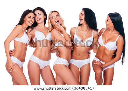 Perfect beauties. Five beautiful women in lingerie posing and looking natural while standing together against white background