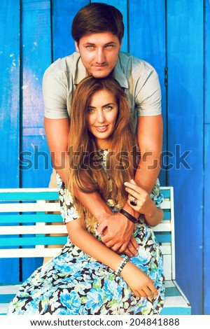 Perfect beautiful couple posing outdoor in hot summer day at blue background, wearing retro outfits, blonde woman and brunet guy . - stock photo