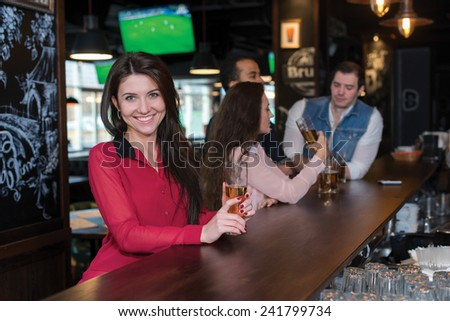 Perfect beer party. Portrait of young beautiful girl is standing in a pub with glass of beer and smiling. Her friends are standing next to her and talking with barman