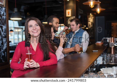 Perfect beer party. Portrait of young beautiful girl is standing in a pub with glass of beer and smiling. Her friends are standing next to her and drinking beer