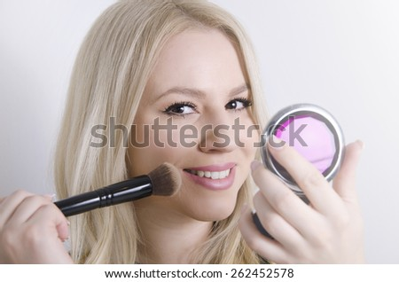 Perfect blonde Caucasian girl putting on makeup, while holding mirror  - stock photo