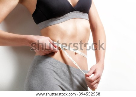 Perfect body of a young women. Beautiful young woman with measuring tape. - stock photo