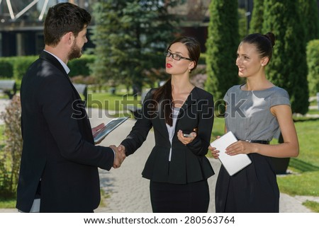 Perfect business relationship. Three confident and motivated business partners are discussing future business details and shaking hands. All are wearing formal suits. Outdoor business concept - stock photo