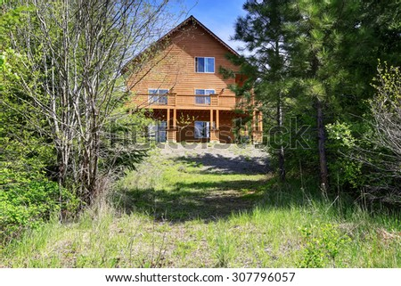 Perfect cabin style home in the woods with lots of greenery.