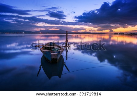 Perfect calm lagoon creates amazing reflection after the sunset with a fisherman boat - specular natural image at the blue hour - focus is on the infinite, boat is moved because it's a long exposure. - stock photo