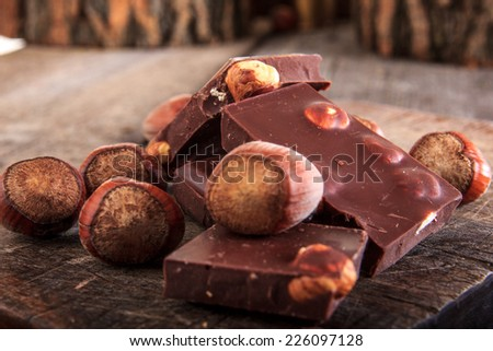 Perfect chocolate with nuts on wooden background, Chocolate bars with hazelnuts - stock photo