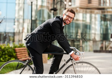 Perfect day for cycling to work. Side view of cheerful young businessman looking at camera and smiling while riding on his bicycle - stock photo