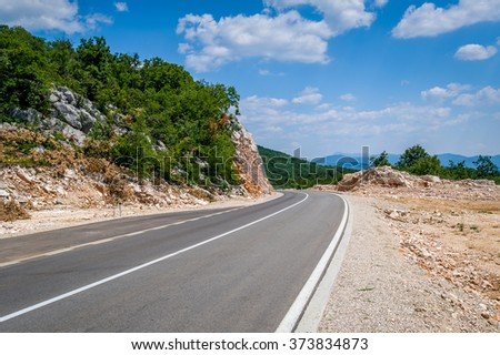Perfect empty mountain road at a hot summer day with a light clouds on a blue sky. Niksic, Montenegro.