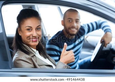 Perfect family car. Shot of a beautiful African woman sitting in a newly bought car with her happy husband smiling cheerfully showing thumbs up