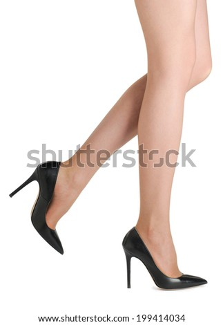 Perfect female legs wearing black high heels isolated on white background. - stock photo