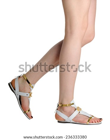 Perfect female legs wearing sandals isolated on white background. - stock photo