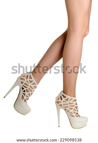 Perfect female legs wearing white high heels isolated on white background.  - stock photo