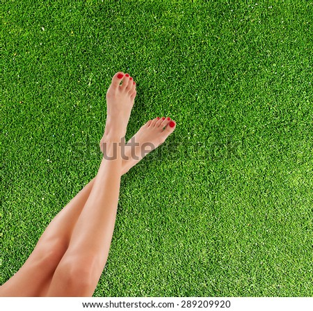 Perfect female legs with summer sandals, placed above grass