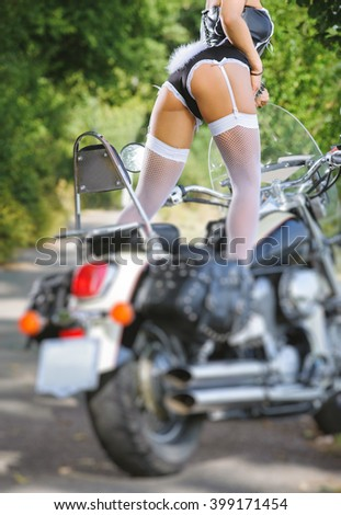 Perfect female sexy buttocks in bunny lingerie. Female biker girl standing on the motorcycle, posing in playboy bunny costume. Back view. Hot outdoors summer day. Tilt shift lens blur effect