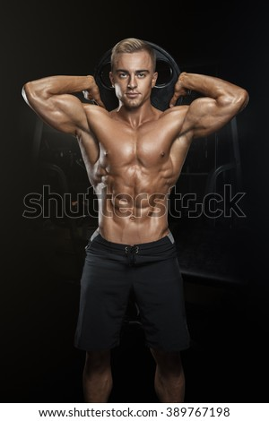 Perfect fit athletic guy posing with barbell plate in gym, perfect lat muscle, shoulders, biceps, triceps and chest. Fitness muscular body isolated on dark background. - stock photo