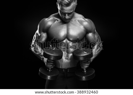 Perfect fit athletic guy workout with dumbbells, perfect abs, shoulders, biceps, triceps and chest isolated on dark background. Black and white photo. - stock photo