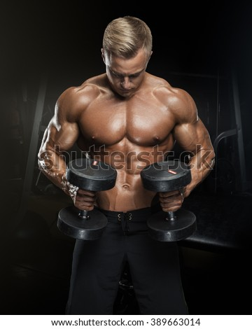 Perfect fit athletic guy workout with dumbbells, perfect abs, shoulders, biceps, triceps and chest. Handsome power athletic man in training pumping up muscles with dumbbells in a gym. - stock photo
