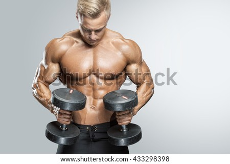 Perfect fit athletic guy workout with dumbbells, perfect abs, shoulders, biceps, triceps and chest. Fitness muscular body isolated on white background. - stock photo