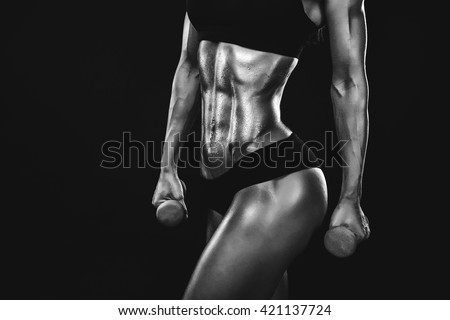Perfect Fitness Body of Beautiful Woman in Drops. Fitness-instructor in Sports Clothing. Female Model with Fit Muscular and Slim Body in Sportswear. Young Fit Girl Lifting Dumbbells. CloseUp - stock photo