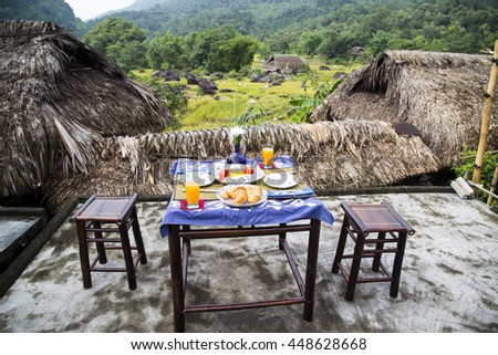 Perfect healthy breakfast on patio in summer day. Orange water, pancakes, bread, melons, mango, dragon fruit on the table against the background of mountains in Vietnam. - stock photo