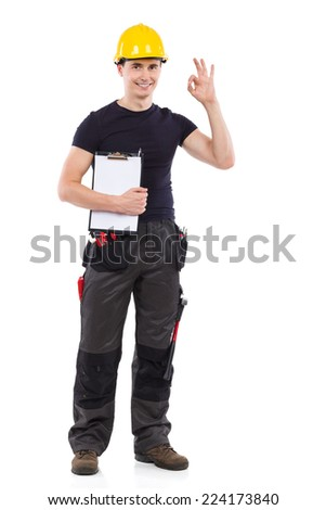 Perfect job! Construction worker in yellow helmet holding clipboard and showing ok sign. Full length studio shot isolated on white. - stock photo