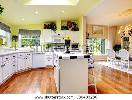 Perfect kitchen with white interior, yellow walls, and glossy hardwood floor.