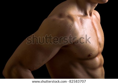 Perfect naked male torso against black background - stock photo