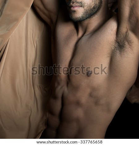 perfect nude body.Perfect naked male torso against black background - stock photo