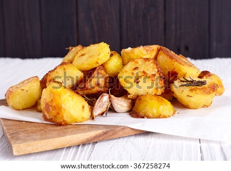 Perfect roasted potatoes with spices, garlic and herbs on wood board that lie on wood background - stock photo