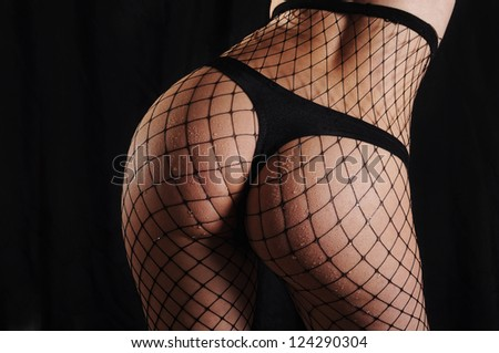 Perfect sexy buttocks in black fishnet tights - stock photo