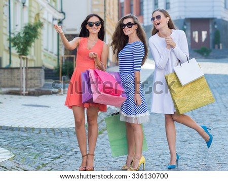 Perfect shopping. Three young pretty stylish girls are holding the shopping bags and looking forward in a good mood. Happy shopping with smiles. Road to mall and dress shops. Ideal shopping on sales - stock photo