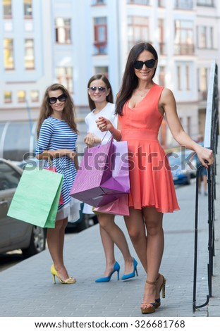 Perfect shopping with a smile. Portrait of  young and pretty girls holding stylish fashionable shopping bags. Shopping sales and perfect mood. Design model fashion bag. Shoping is fun. Glassess
