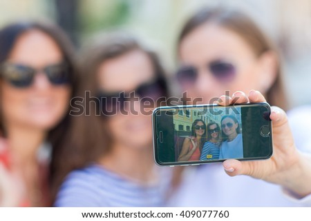Perfect shopping with a smile. Young and pretty stylish girls are holding the shopping bags and making selfie on a sell phone. Happy shopping with smiles. Mall and sales
