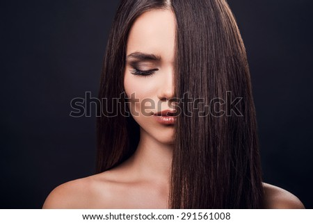 Perfect silky hair. Beautiful young shirtless woman keeping eyes closed and covering half of face by hair while standing against black background   - stock photo