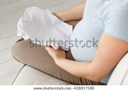 Perfect size. Cropped shot of a pregnant female sitting on the sofa holding  baby t-shirt indoors. - stock photo
