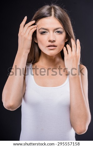 Perfect skin. Beautiful young  touching face and looking at camera while standing against dark background. - stock photo