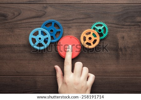 perfect solution concept. colorful gears and hand on the brown wooden background - stock photo