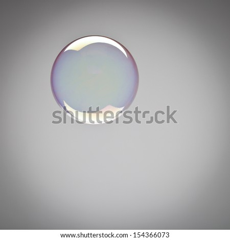 Perfect spherical shining soap bubble with iridescent reflections suspended mid air over a grey background with copyspace and vignetting