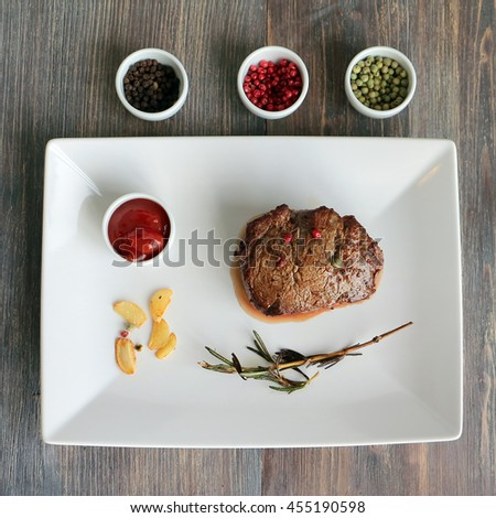 Perfect steak on a white plate with tomato sauce, roasted garlic, rosemary and three color pepper in corns - red, black and green in small bowls on a wooden table - stock photo