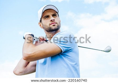 Perfect strike. Low angle view of young golfer swinging his driver and looking away with blue sky as background - stock photo