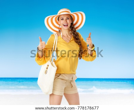 Perfect summer. happy active woman in shorts and yellow blouse with white beach bag on the beach showing thumbs up