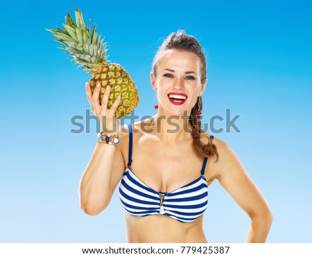 Perfect summer. Portrait of smiling healthy woman in swimsuit on the beach with pineapple
