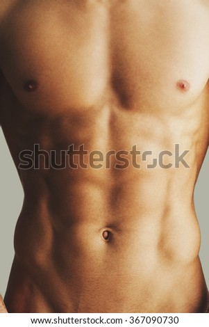 Perfect torso. Close-up of muscular man with perfect torso standing against grey background - stock photo