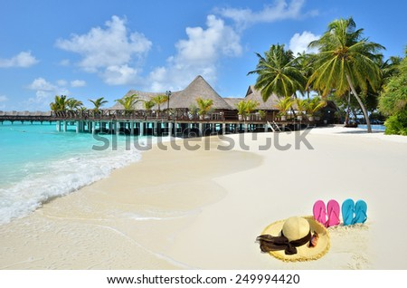 Perfect tropical vacations -- Sunhat with sunglasses and flip flops at the beach  - stock photo