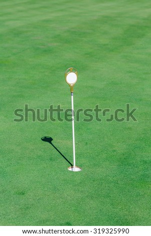Perfect wavy green ground with a flag on golf course  - stock photo