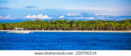 Perfect white beach with turquoise water and big palms on beach - stock photo
