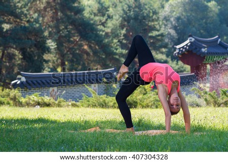 Perfect yoga flexibility. Beautiful young girl is balancing doing yoga and showing her flexibility. Yoga outdoor class workout
